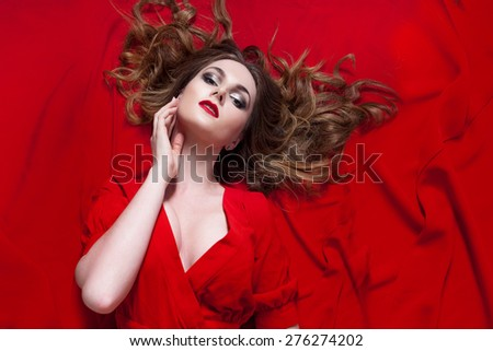 Woman in red dress posing with waving fabric, horizontally - stock photo