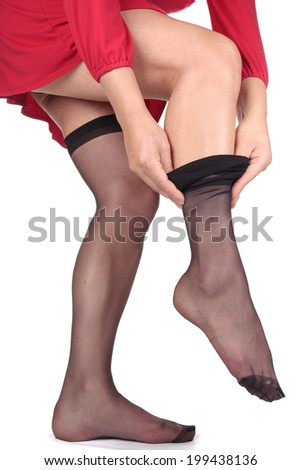 Woman in red dress putting on stockings - stock photo