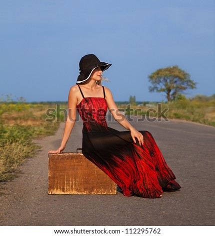 woman  in red dress waiting on the road with her baggage