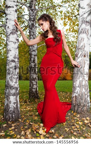 Woman in red dress walking in autumn park