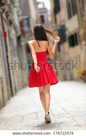 Woman in red dress walking in street in Venice, Italy cheerful and happy in rear view showing back of sundress. Pretty sexy brunette fashion model girl in her 20s. - stock photo