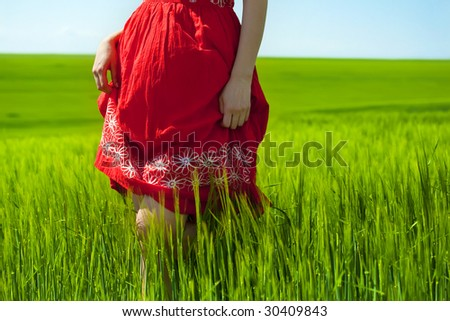 woman in red dress walking through green field - stock photo