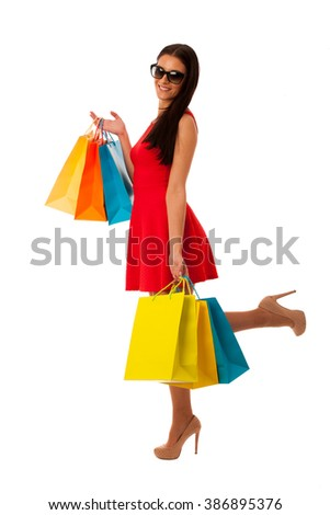 Woman in red dress with shopping bags excited of purchase in mall. - stock photo