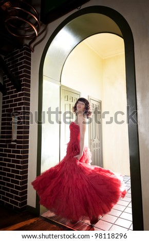 Woman in red evening dress at the door - stock photo