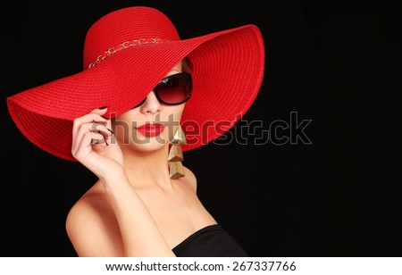 Woman in red hat and sunglasses over black background - stock photo