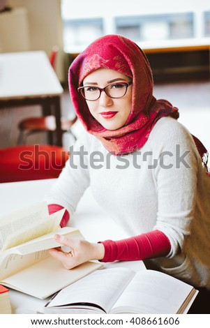 Woman in red head scarf studying at the university - stock photo
