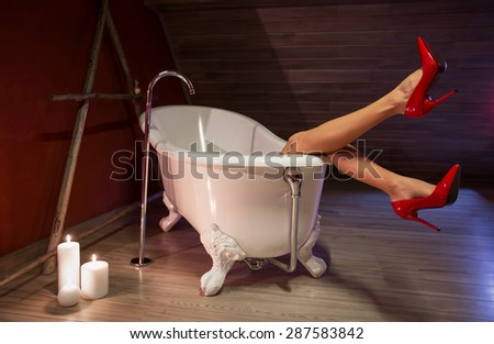 Woman in red high heel shoes in bath - stock photo