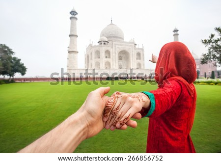 Woman in red Indian costume holding her friend by hand and pointing to Taj Mahal in Agra, Uttar Pradesh, India - stock photo