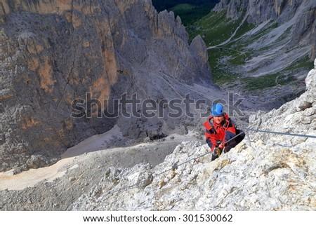 """Woman in red jacket climbs via ferrata """"Merlone"""", Cadini di Misurina, Dolomite Alps, Italy - stock photo"""