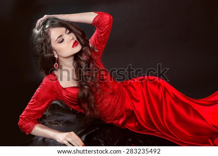 Woman in red lying in the dark. Fashion tempting girl model in sexy gown with sensual lips and long hair isolated on black background.