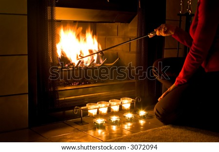 Woman in red sweater stoking a fire in the fireplace with candles burning in front - stock photo