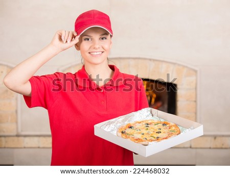 Woman in red uniform is holding a whole pizza in hand and asking you to ordering a pizza. - stock photo