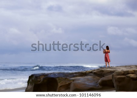 Woman in red vintage summer sun dress standing on a rock bluff along the sea coast watching surfers and enjoying the tropical California waves of the Pacific ocean