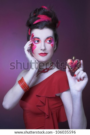 Woman in red. Young lady with artistic make-up and with feathers in her hair.