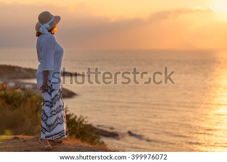 Woman in retro hat standing and watching towards the sun peaceful sunset during your holiday on Greek coast of Aegean sea. - stock photo