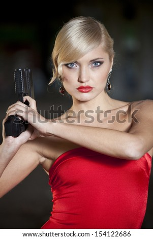 woman in retro look and red dress holding a handgun - stock photo