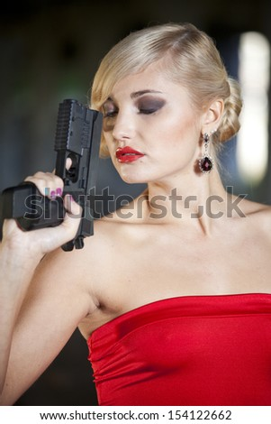 woman in retro look holding a handgun close to her face in thinking position - stock photo