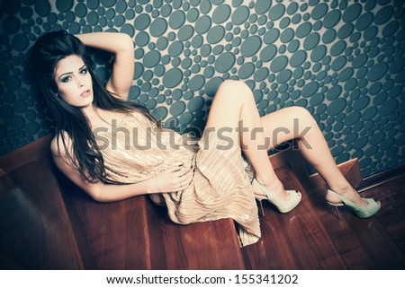 woman in retro style golden dress and high heel shoes sit on stairs full body shot indoor - stock photo
