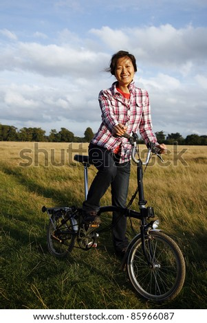 Woman in Richmond Park cycling at dusk - stock photo