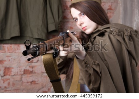 Woman in Russian military uniform shoots a rifle. Female soldier during the second world war. - stock photo