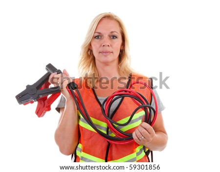 Woman in safety vest holding car jumper cables over white background - stock photo