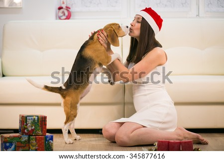 woman in santa helper hat with her beagle