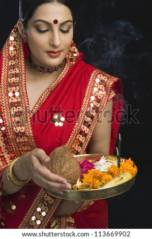 Woman in sari holding religious offering - stock photo