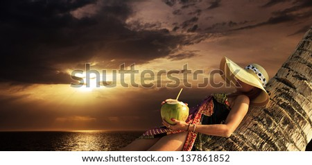 Woman in sarong resting on a coconut tree on the beach at sunrise in Thailand - stock photo