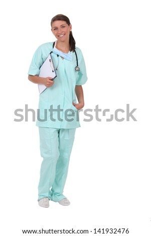 Woman in scrubs with stethoscope and clipboard - stock photo