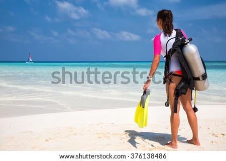 Woman in scuba diving gear standing on a maldivian beach facing the ocean - stock photo