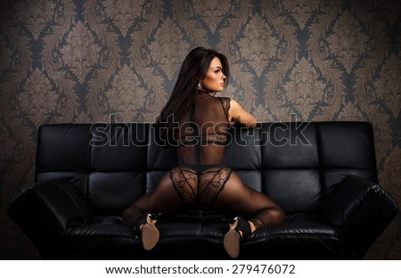 Woman in sexy lingerie on a leather sofa - stock photo