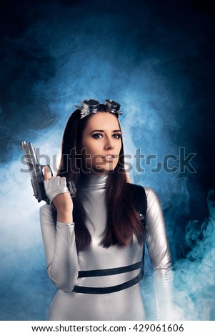 Woman in Silver Space Costume Holding Pistol Gun - Portrait of sci-fi retro futuristic girl with firearm  - stock photo