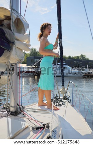 Woman in skirt stands on yacht during sailing on river at sunny summer day