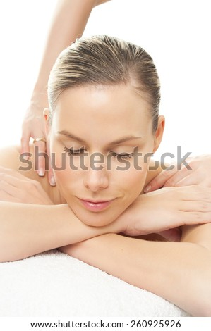 Woman in spa getting shoulders massage. Relaxation concept over white background. - stock photo