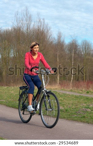 Woman in sports cloths cycling in a park. - stock photo