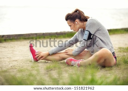 Woman in sportswear outdoors stretching her legs before running - stock photo