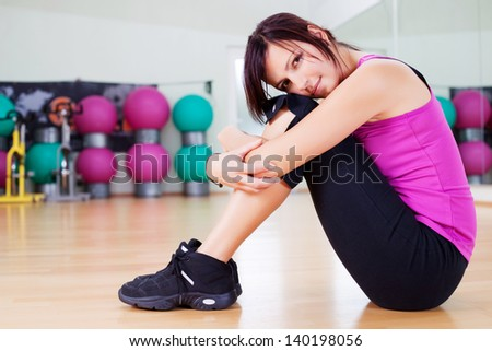Woman in sportswear resting head on her knees after working out - stock photo