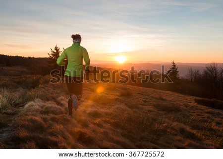 woman in sportswear running for fitness on the trail in the mountains with sunset with flares in the evening