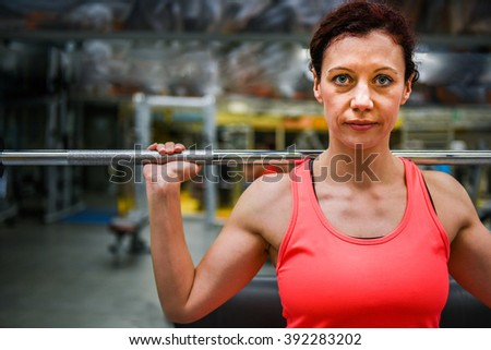 Woman in sportswear training in gym holding bar making weight-lifting exercises indoor. - stock photo