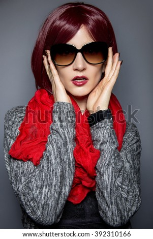 Woman in spring or fall fashion wearing retro style sun glasses.  The sunglasses are vintage style.  The image is lit with a slight vignette to bring focus to subject. - stock photo