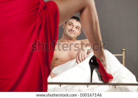 woman in stiletto seducing man in bed - stock photo