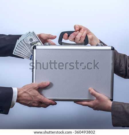Woman in suit giving briefcase with dollars to man - stock photo