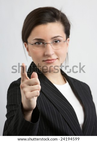 Woman in suit pointing at camera DOF focus on hand - stock photo