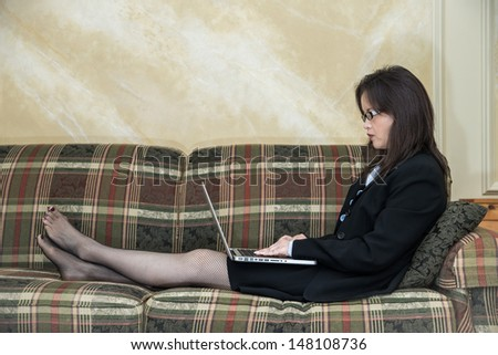 Woman in suit relaxing on sofa with laptop at home - stock photo