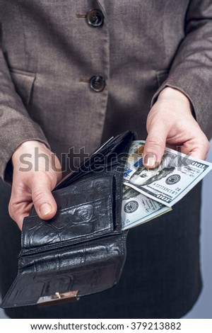 Woman in suit with leather wallet full of US dollars. Conception of safe storage and protection of cash. Financial theme. Vertical view. - stock photo