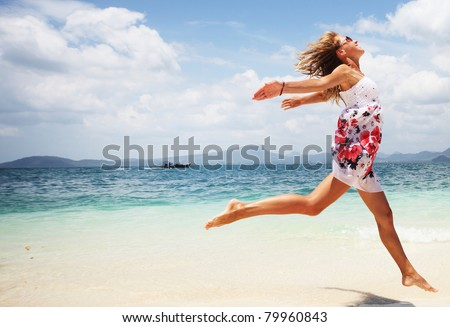 Woman in summer dress jumping over wet sand by tropical sea