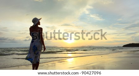 Woman in summer dress standing on a sandy beach and looking to the horizon - stock photo