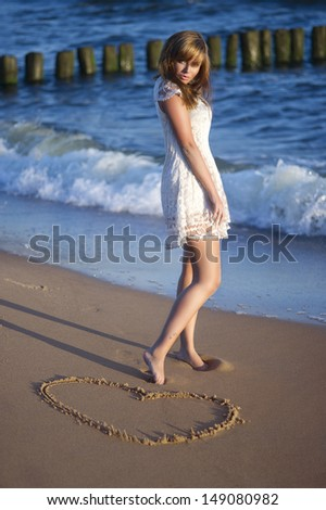 Woman in summer dress standing on a sea coast  - stock photo
