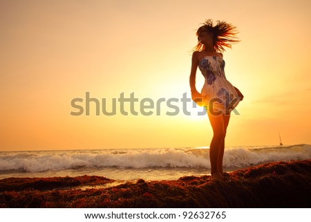 Woman in summer dress standing on a sea coast and enjoying a tropical waves - stock photo
