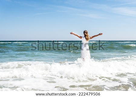 Woman in summer dress standing on a sea coast and looking to the horizon - stock photo